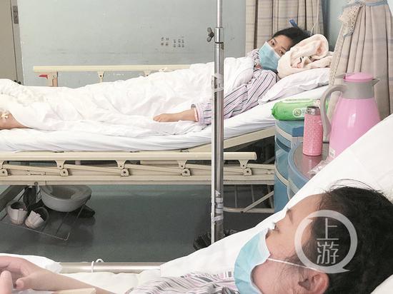手术后的母亲隔着病床看着女儿。