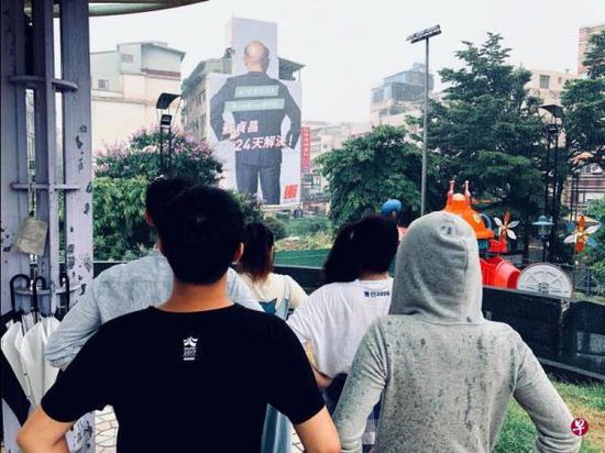 民进党新北市长参选人苏贞昌位于新北市新庄区的大型竞选看板,高五层楼、宽12公尺,视觉意象罕见使用苏贞昌手插腰的背影照,吸引不少往来民众驻足拍照模仿。(新加坡《联合早报》网站)