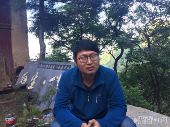 小胡坐在悬崖边的瑞云庵外接受采访。记者杨安平摄