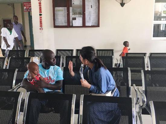 2018年7月18日,中国援建塞内加尔儿童医院候诊室,苏利曼·费迪奥尔抱着孩子承受记者采访。(新华社记者蒋国鹏摄)