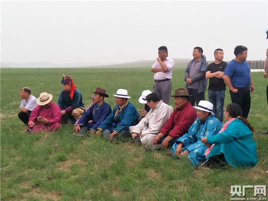 农牧民冒雨席地而坐欣赏表演 央广网记者王晶 摄