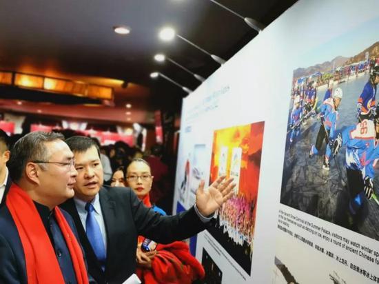 我驻洛杉矶总领事张平大使(左)观看北京冬奥会和冬残奥会图片展