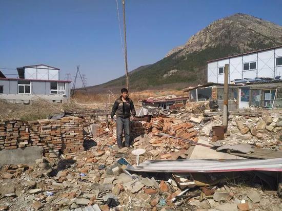 ▷裘国金站在酿成一片废墟的家中