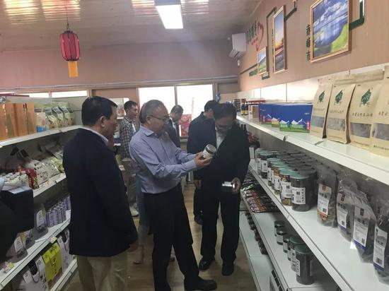 王荣武(中)查看展销产品。图/兴安日报