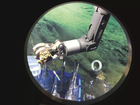 """2017年5月25日,""""蛟龙""""号载人潜火器正在马里亚纳海沟""""应战者深渊""""北坡下潜,获得岩石样品。图/新华"""