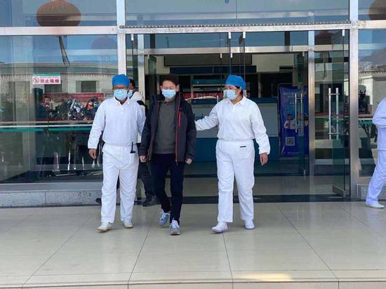 张某某在医生陪伴下,走出自治区第三人民医院。徐驭尧摄