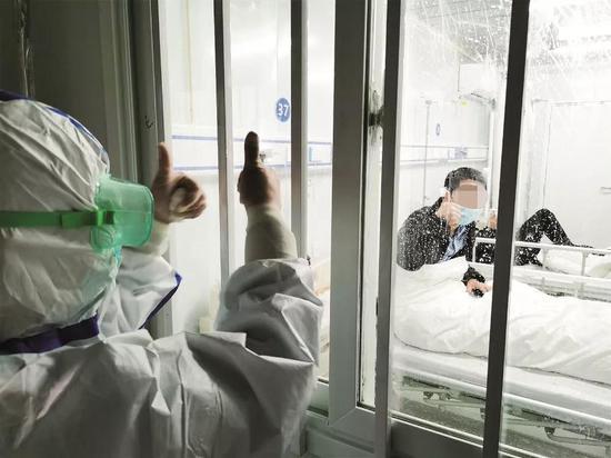 2020年2月9日晚,武汉雷神山医院吸收了第二批新冠肺炎患者,总入住患者达80余人。图为医护职员为患者鼓劲加油。图/中新