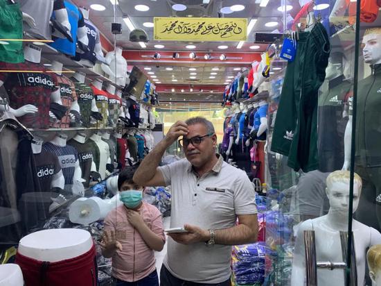 5月6日,运动服装批发商侯赛因在自己的服装店内。新华社记者 张淼 摄
