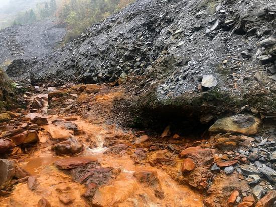 安康市白河县凤凰村露天堆放的矿渣到处可见,有矿渣的处所流水就呈土黄色,PH值表现为强酸性。