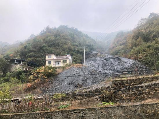白河县凤凰村一户建在矿渣旁边的新房。