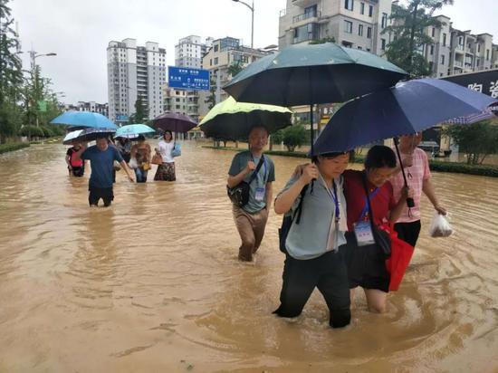 7月7日,安徽歙县,监考老师和学生正在去考点的路上。