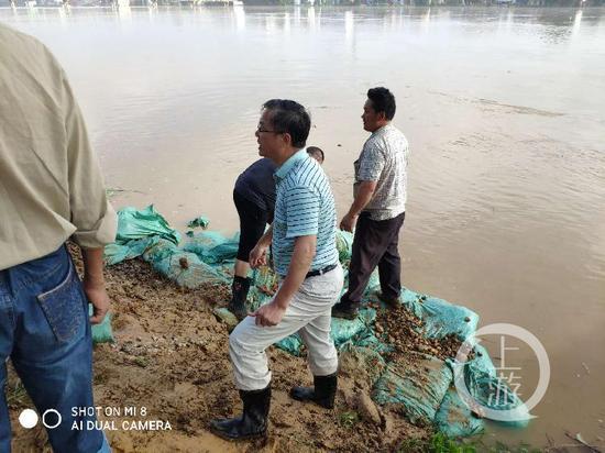 ▲吴俊亮在抗洪一线查看洪水。图片来源/鄱阳县水利局