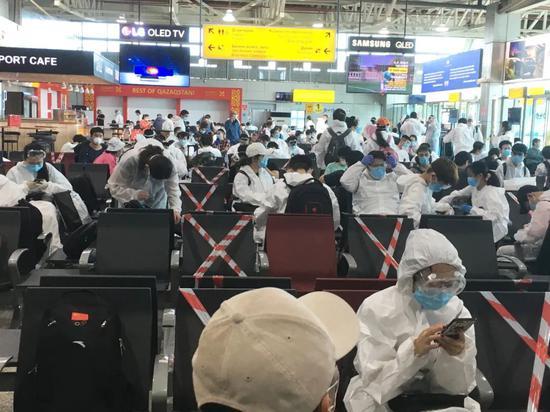 阿拉木图机场候机厅,许多人穿着防护服。