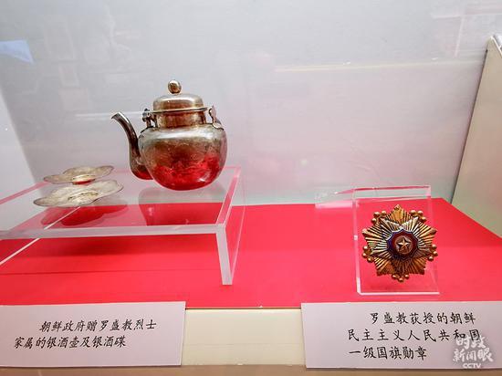 △左为朝鲜当局赠给罗盛教义士家族的银酒壶、银酒碟,右为罗盛教获授的朝鲜民主主义人民共和国一级国旗勋章。(总台央视记者荆伟拍摄)