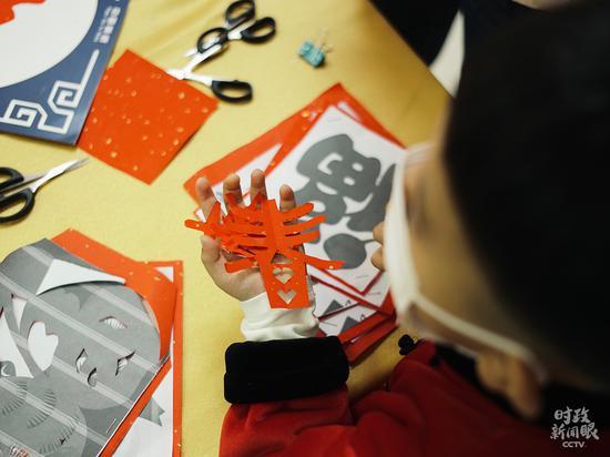 △孩子们在社区运动室演习剪纸。(总台央视记者王哈男拍摄)
