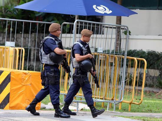 11日,安保人员在一家酒店外警戒。新华社记者李鹏摄