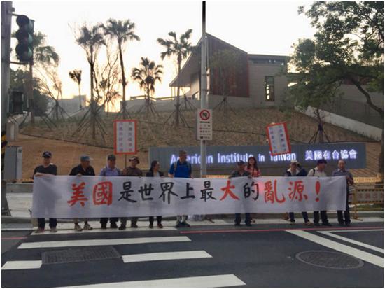 图:12日,AIT台北新址落成仪式现场,有抗议人士拉起横幅