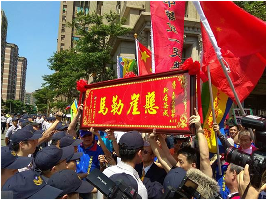 """图:张安乐率众手持""""悬崖勒马""""匾额讽刺AIT台北新址落成"""