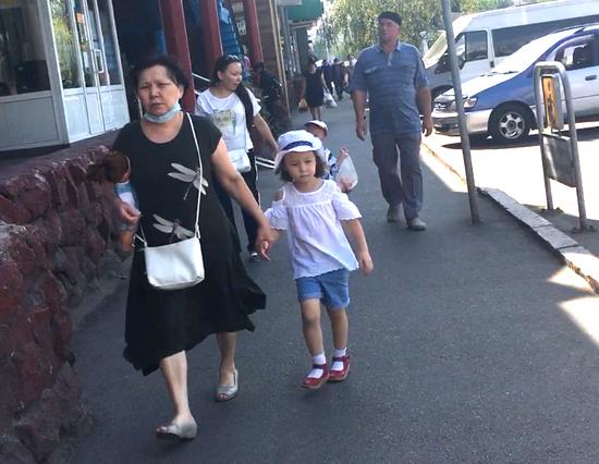 哈萨克斯坦疫情至今未得到有效控制,随处可见未带口罩的市民。