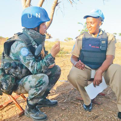 2017年11月29日,中國第四批赴南蘇丹(朱巴)維和步兵營女兵班班長于培傑(左)在執行武器禁區巡邏任務休息期間,與共同執行任務的聯合國員警交流心得體會。王理紅攝
