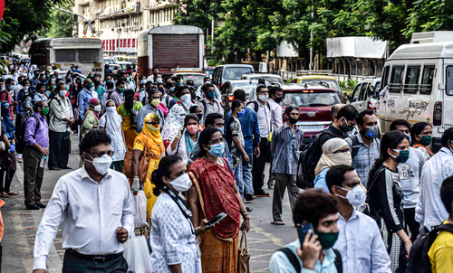 6月9日,佩戴口罩的乘客在印度孟买的公共汽车站候车。新华社发