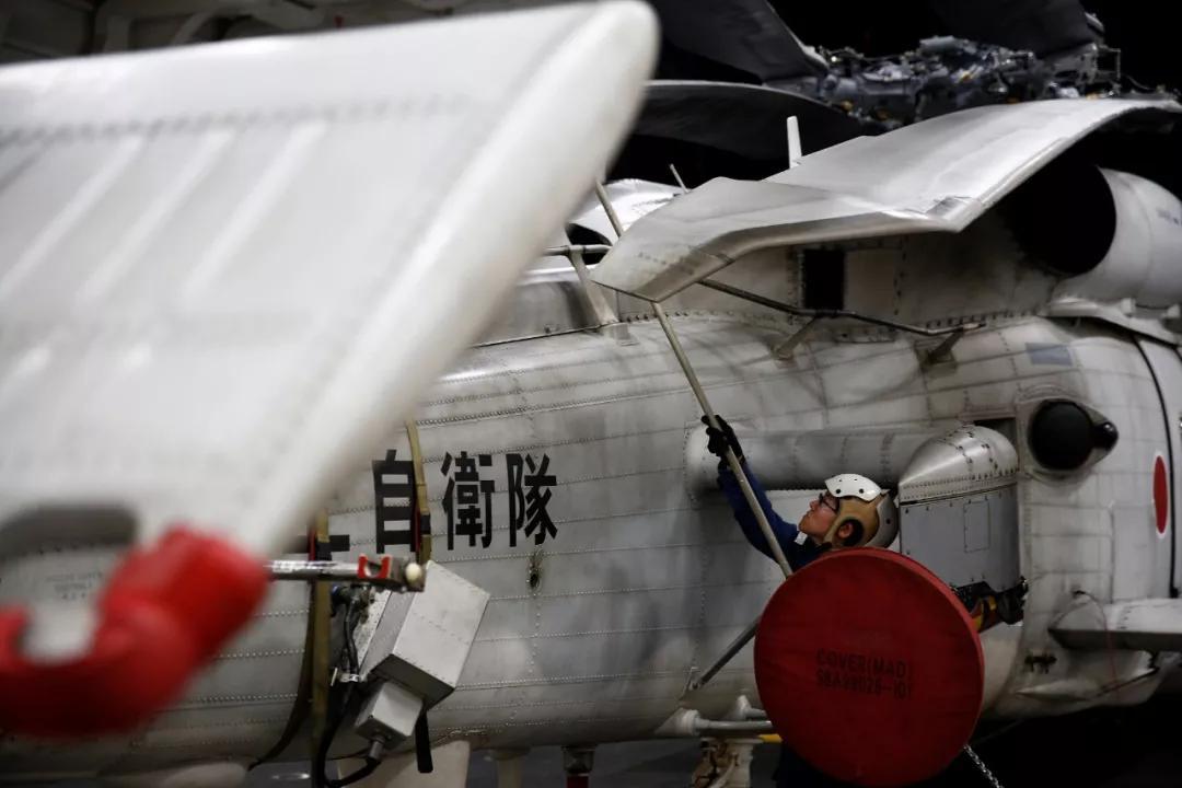 """▲當地時間2018年9月23日,印度洋,在日本""""加賀""""號直升機航母的機庫甲板上,一名女性維修專家在一架SH-60K海鷹直升機上工作。圖據視覺中國"""