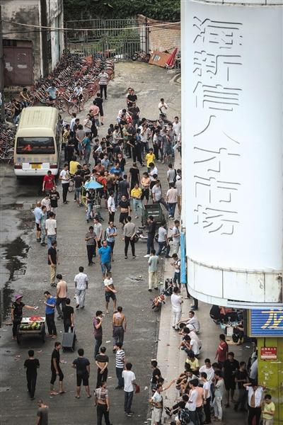 """8月14日早晨5点40分,海新信人才市场旁的街道上,已经围满了前来""""抢""""薪水日结工作的打工者。本版采写、摄影/新京报记者 彭子洋"""
