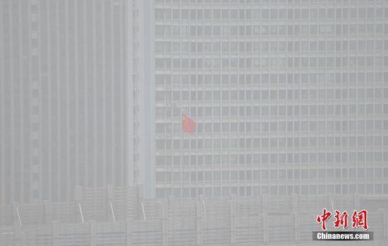 12日上午,雾霾之中的高楼建筑前,红旗飘扬。