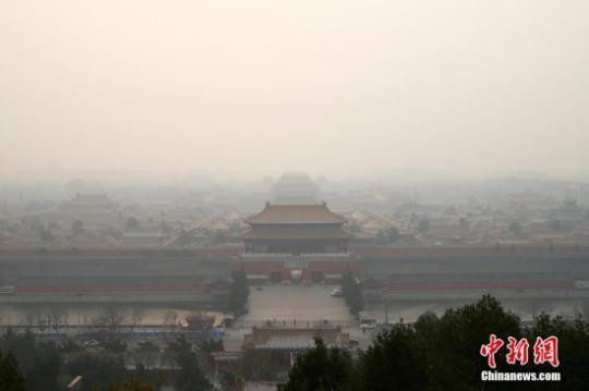 材料图:2015年12月7日,北京遭逢重净化气候,故宫覆盖在一片雾霾之下。中新社记者 张远 摄