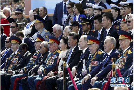 图为:2015年5月9日,俄罗斯举行纪念卫国战争胜利70周年盛大庆典。国家主席习近平和来自世界约20个国家和地区及国际组织领导人出席庆典。这是习近平和夫人彭丽媛同普京等领导人出席红场阅兵仪式。新华社记者 鞠鹏 摄