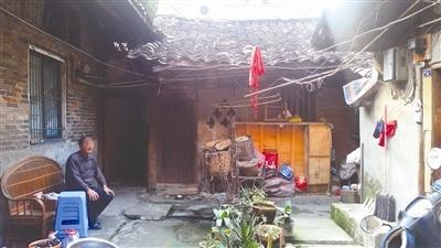 王怀坐在租的房屋外
