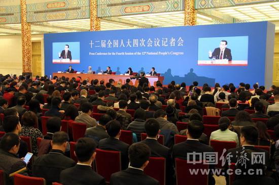 主席台背景墙上嵌入了两块大屏幕,播放总理答问的特写镜头。(中国经济网记者李焱 摄)