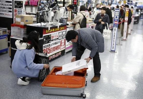 """国家旅客赴日""""爆买""""诱发天下人大代表热议。图为国家旅客在东京一家赆赀中购物后装箱。(路透社)"""