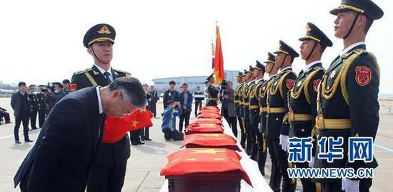 3月31日,在韩国仁川国际机场,中国驻韩国大使邱国洪(左前)向中国人民志愿军烈士遗骸默哀。新华社记者 姚琪琳 摄