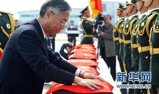 3月31日,在韩国仁川国际机场,中国驻韩国大使邱国洪为烈士遗骸棺椁覆盖国旗。 新华社记者 姚琪琳 摄