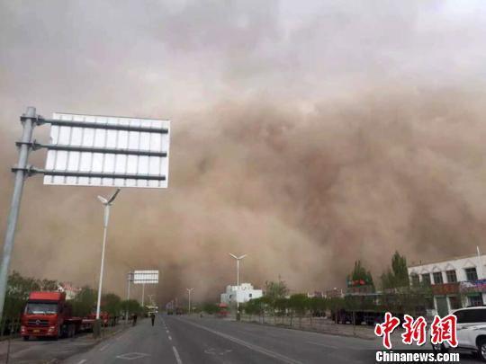 """4月15日下午,位于甘肃河西走廊最西端的酒泉市多地出现沙尘天气。图为瓜州县出现了巨大""""沙尘墙""""滚滚推进。 钟欣 摄"""