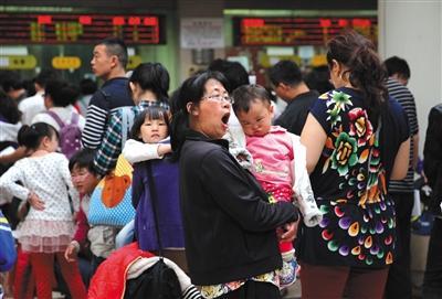 儿童医疗资源短缺是我国医改面临的难题之一。图为2014年5月9日,首都儿科研究所,一位家长抱着孩子排队挂号。资料图片/新京报记者 薛珺 摄