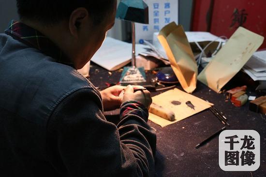 张国维的工作室位于琉璃厂的一间平房里,一盏老台灯、几方印章、几把刻刀,陈设非常简单。千龙网记者 马文娟 摄