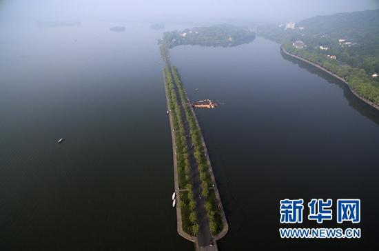 """航拍杭州西湖景区的白堤(5月11日摄)。杭州自古多桥。断桥、长桥、钱塘江大桥、复兴大桥……古朴文雅辉映现代气派,透出这座城市融汇古今、灵动开放 的底蕴。举世瞩目的二十国集团(G20)领导人第十一次峰会将在这里举行。有趣的是,这次峰会的会标,也是一座桥——一座由20个成员搭起的""""桥""""。这会 是一座怎样的桥?它能否缓解当前全球经贸河道上的种种淤塞?它能否跨越发达国家和发展中国家之间的沟沟壑壑? 全球在期待,中国在行动。新华社记者黄宗治摄"""