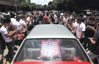 """民主中路,一位男子前来反对爱狗人士,他的车后玻璃上贴着一个""""悲""""字。"""