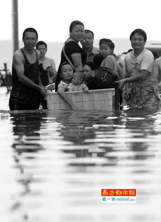 """7日上午,武汉市南湖假日小区的被困居民利用自制""""小船""""转移。"""