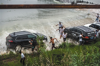 昨日,梁子湖与牛山湖隔堤正式实施爆破作业,完成分洪,人们躲避爆破后激起的余浪。新华社记者 肖艺九 摄