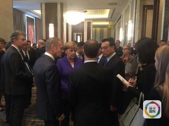 7月15日,李克强总理在会场过道与多位领导人交谈。
