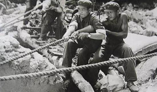 在没有大型起重工具的情况下,解放军战士用双手拨开重物救人
