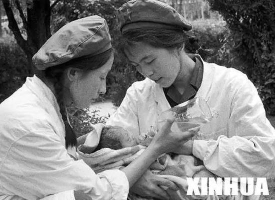 解放军某部的医务人员在护理地震后第二天出生的婴儿