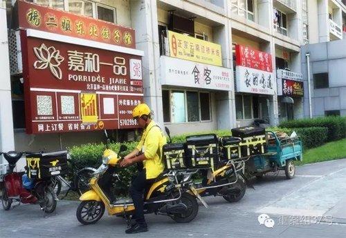 2016年7月26日,通州区北京像素小区,一栋楼的一楼开了密集的餐馆,餐馆外停着美团的外卖车,一名送餐员正要骑车去送餐。