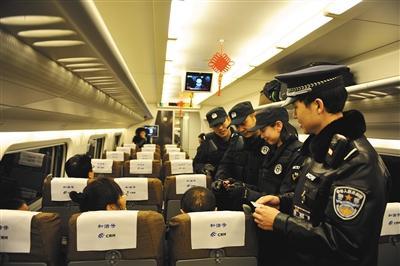 2015年1月8日,在呼和浩特开往包头的动车上,呼和浩特铁路公安处乘警正在对旅客的身份证进行查验。图/视觉中国