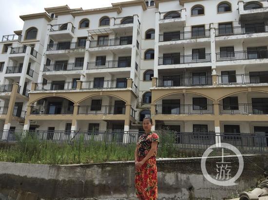 重庆购房者雷秀英站在独居的烂尾楼前合影,左上角晾晒有衣服的就是她居住的房间。