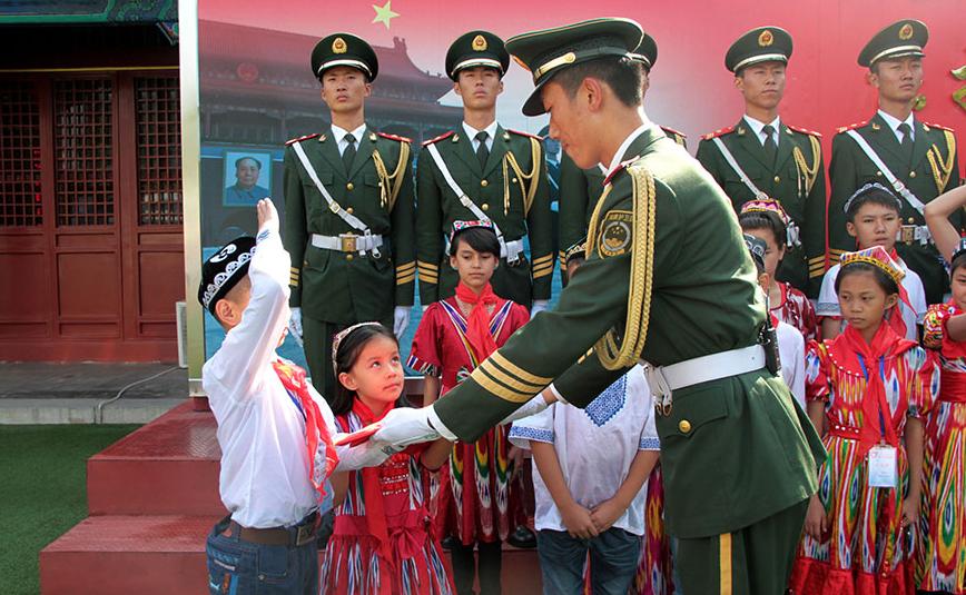 2014年09月24日,北京,国旗护卫队员向维族少年赠送国旗。