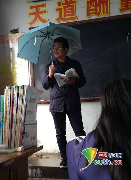 老师打伞上课。
